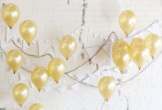 Photo of gold balloons on a white wall