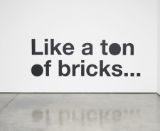 Photo of the words 'Like a ton of bricks...' on a white wall