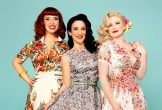 Phot0 of the 3 Puppini Sisters agains a teal background