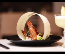 Photo of a prawn on a black plate next to a cocktail