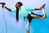 A woman balances on one leg holding a hair dryer