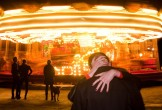 Photo of a couple kissing in front of a carousel