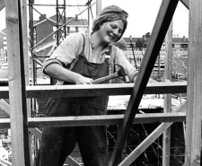 Black and white photo of a woman working on a building site