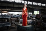 A woman in a red dress stands in a warehouse