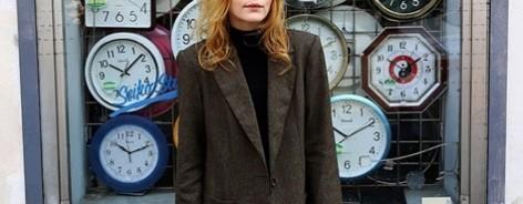Jessica Pratt with oversized jacket infront of clocks