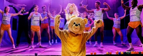 Teddy bear dances in ball pit in front of stage