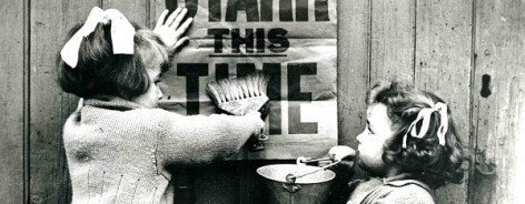 Black and white photo of two girls with poster
