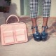 A woman in heeled shoes and a pink handbag
