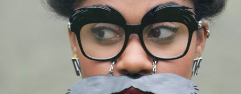 Woman wears glasses and a fake moustache
