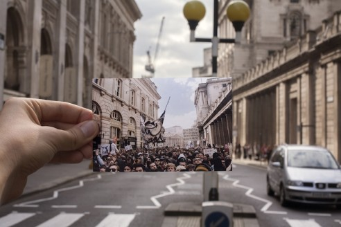 Someone holds a photograph of a once crowded, now empty street.
