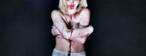 A girl stands in pants with blood on her face