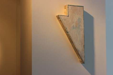 Wooden and painted arrow shape on a wall