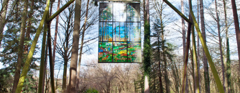 Photo of a stained glass window hanging in the trees