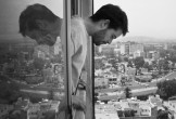 Black and white shot of a man leaning out of a window