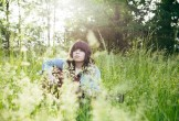 Photo of singer Samantha Craine in a field with guitar
