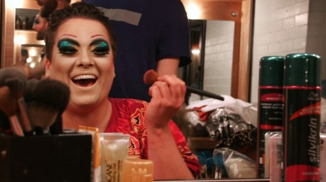 A drag queen doing her makeup in a mirro