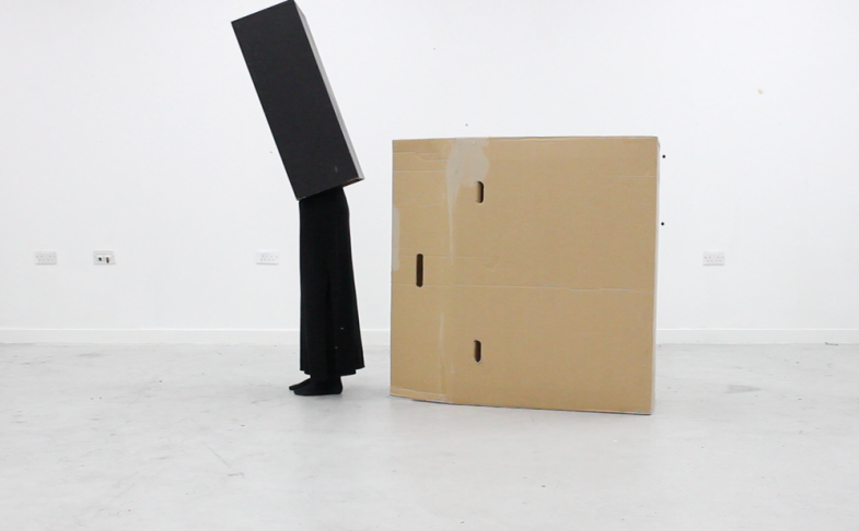 Image of person in a black box, with a cardboard box beside