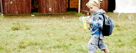 Small boy with bubble blower and headdress
