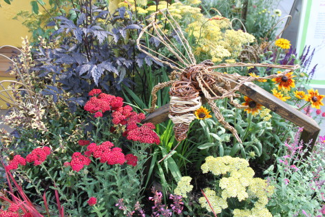 Flower bed with wooden bee