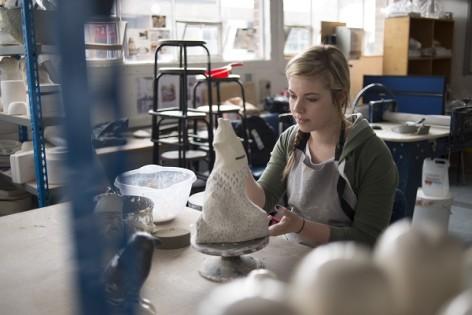 Photo of designer-maker Jasmine with a ceramic in her studio
