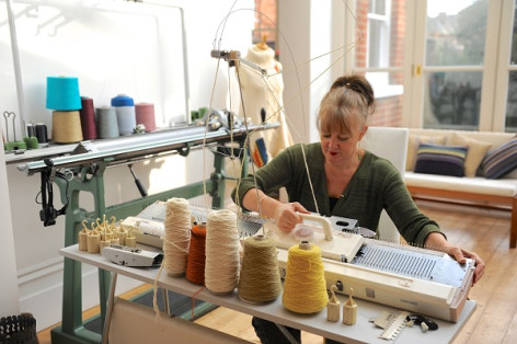 Photo of designer-maker Judith Wilson at work on the loom