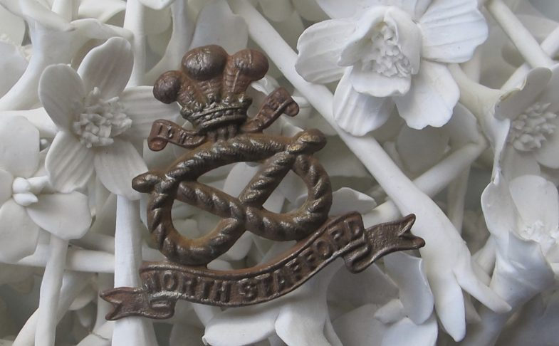 Photo of white bone china flowers and a medal