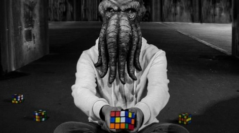 Photo of man with squid head holding rubix cube