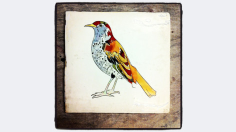 A ceramic tile with a bird on it
