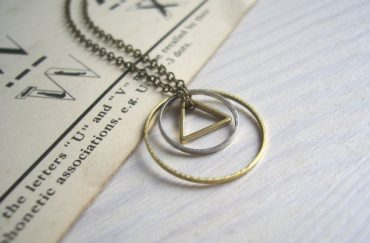 A necklace with two circles and a triangle