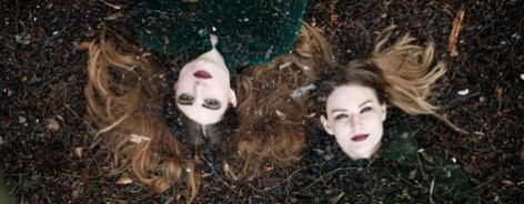 Two women lie on their back looking upwards