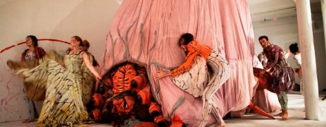 Photo of performers moving a large pink sculpture