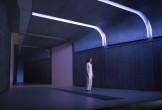 A woman in white in a stark corridor