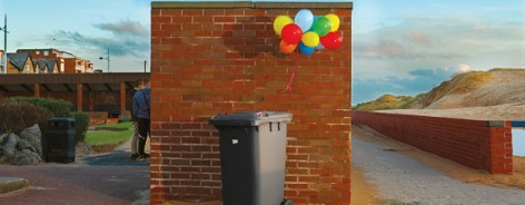 A wheelie bin with ballons tied to it