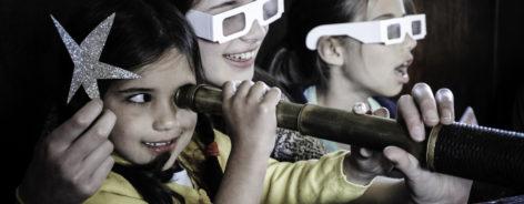 Three children looking through telescope