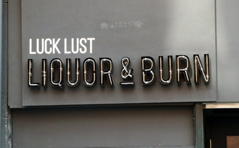 Image of the signage outside of Manchester's Luck Lust Liquor and Burn