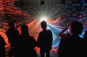 Silhouette of people standing in front of an exhibit at Manchester Science Festival 2018