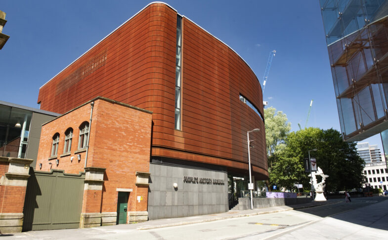 The Corten exterior of People's History Museum on a sunny day beneath blue skies