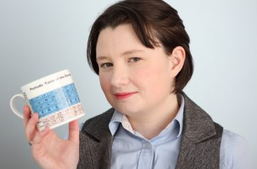 Photograph of poet and scientist Rachel McCarthy holding a mug showing the periodic table of elements.