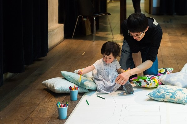Adult and child drawing on the floor as part of the Family Weekend event