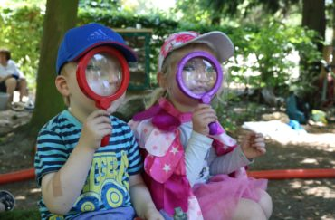 Little explorer at YPS, two children with large magnifying glasses in front of their faces