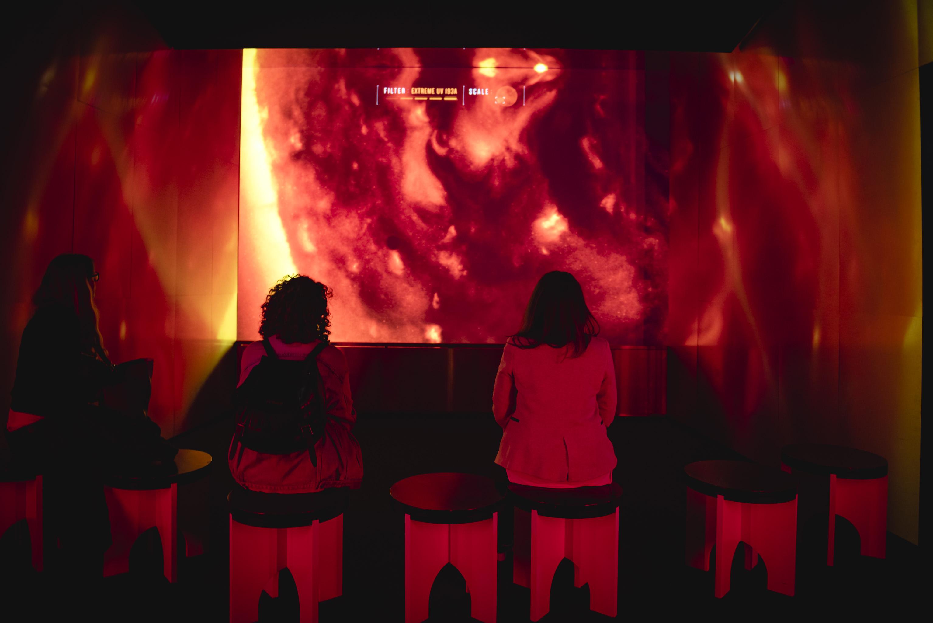 Half term fun - People sat on stools watching film footage the sun