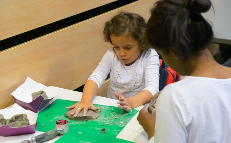 child rolling clay at a table in a Family work