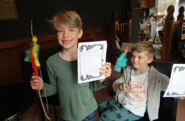 Grimm & Co event - two children shown holding crafts they've made