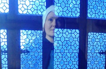 Hallowtide activities at Little Moreton Hall. Woman's reflection shown in a window.