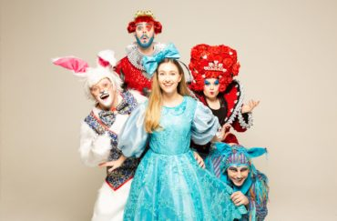 Alice in Wonderland at Waterside Arts. Alice is shown in a blue dress characters from the story behind her including the white rabbit and the Queen of Hearts. Part of our half term in Manchester activities
