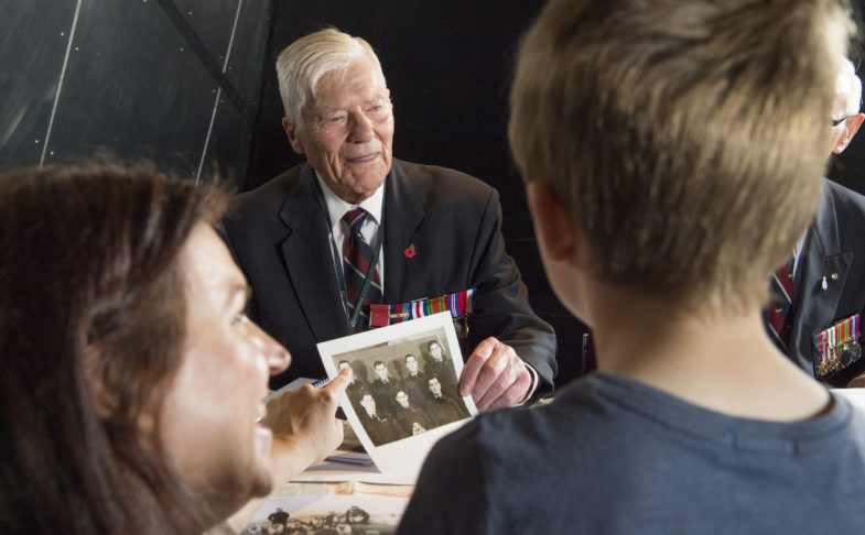 A young boy and a woman meet a veteran in the meet the veterans event at IWMN