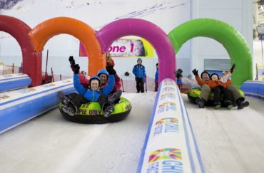 People sliding down the slopes at Chill Factore on an inflatable ring