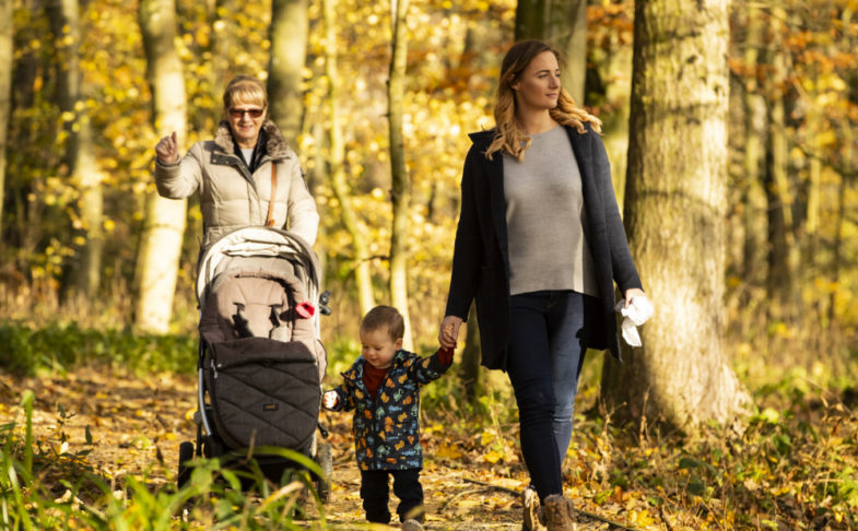 A family walking along a path in the woodlands trail at Lyme Park.