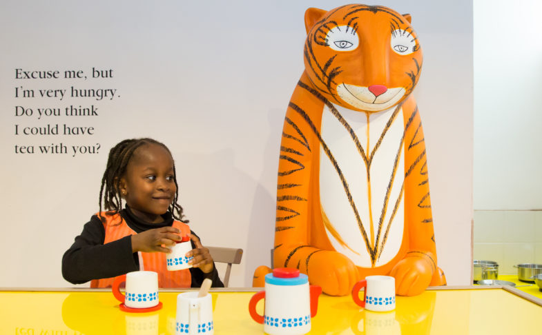 Half term fun - Young girl sat next to the tiger as part of the The Tiger who came to tea and the adventures of mog the forgetful cat exhibition