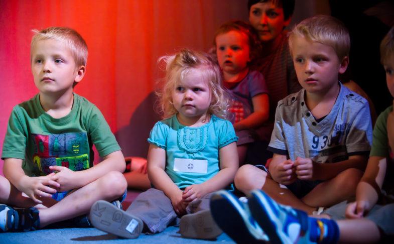 Children sat on the floor for Under the Rainbow activity